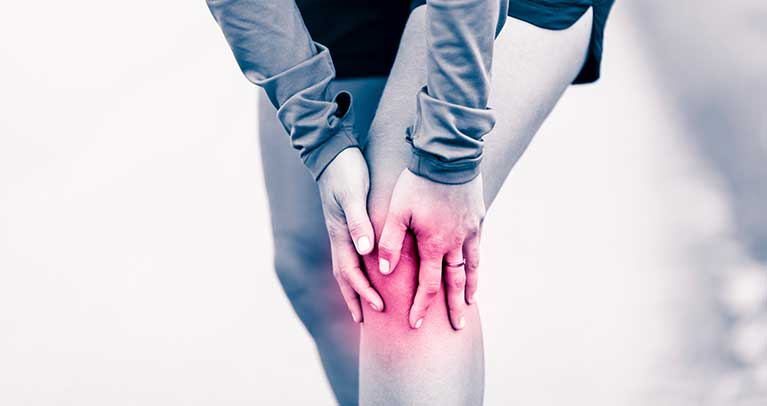 Image of a person holding there knee as if in pain.